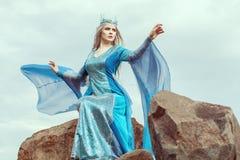 Den härliga älvakvinnan sitter överst av ett berg royaltyfria bilder