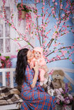 Den härliga affärsdamen i klassisk dräkt spelar med hennes söta litet behandla som ett barn royaltyfri bild