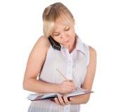 Den härliga affärskvinnan är handstil i anteckningsboken Royaltyfri Bild