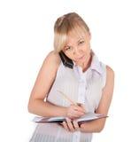 Den härliga affärskvinnan är handstil i anteckningsboken Arkivfoton