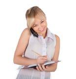 Den härliga affärskvinnan är handstil i anteckningsboken Arkivfoto