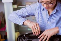 Den härliga affärskvinnan öppnar portföljen Arkivfoto