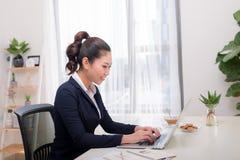 Den härliga affärskvinnan använder en bärbar dator och ler medan woren royaltyfri fotografi