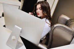 Den härliga affärskvinnan i en vit skjorta och exponeringsglas på arbetsplatsen på datoren övervakar Royaltyfri Bild