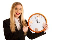 Den härliga affärskvinnan rymmer en klocka som ett tecken för tidrätta Royaltyfri Fotografi