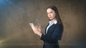 Den härliga affärskvinnan ser in i ett handlagblock, brun bakgrund Royaltyfri Bild