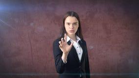 Den härliga affärskvinnan skjuter en osynlig knapp, grå bakgrund Royaltyfri Bild