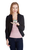 Den härliga affärskvinnan som rymmer det lilla huset gömma i handflatan på. Royaltyfri Bild