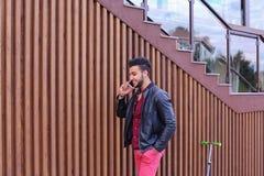 Den härliga affärsmässiga muslimska mannen går och talar vid telefonen och S Royaltyfri Foto