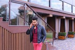 Den härliga affärsmässiga muslimska mannen går och talar vid telefonen och S Arkivbilder