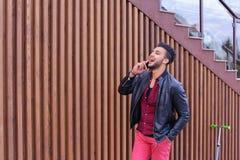 Den härliga affärsmässiga muslimska mannen går och talar vid telefonen och S Royaltyfria Bilder