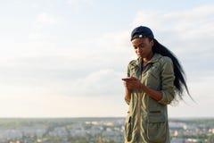 Den härliga afrikansk amerikanflickan lyssnar till musik och att koppla av Le den svarta damen för barn på suddig stadsbakgrund Fotografering för Bildbyråer