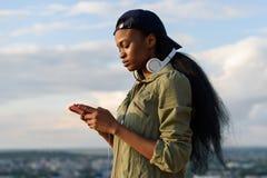 Den härliga afrikansk amerikanflickan lyssnar till musik och tycker om Le den unga svarta kvinnan på suddig stadsbakgrund arkivfoto