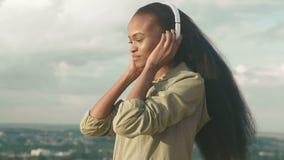 Den härliga afrikansk amerikanflickan lyssnar till musik och tycker om Le den svarta flickan för barn på suddig stadsbakgrund Royaltyfri Foto