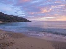 Den härliga apelsinen för pastellfärgade rosa färger och den guld- solnedgången fördunklar och vinkar på den Agios Georgios Pagon royaltyfria foton