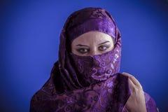 Den härliga arabiska kvinnan med traditionellt skyler på hennes framsida, intens Arkivfoton