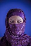 Den härliga arabiska kvinnan med traditionellt skyler på hennes framsida, intens Arkivbild