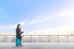 Den härliga asiatiska affärskvinnan som sitter på den blåa resväskan, rymmer minnestavlan och arbetet på modern terrass arkivfoton