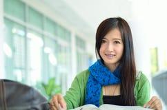 Den härliga asiatiska flickan är avläsning och leendet Arkivbild