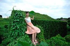 Den härliga asiatiska flickan strosar i växtväggen royaltyfri foto