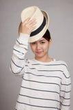 Den härliga asiatiska flickan tar av en hatt Fotografering för Bildbyråer