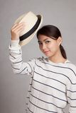 Den härliga asiatiska flickan tar av en hatt Royaltyfria Bilder