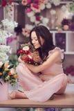 Den härliga asiatiska kvinnablomsterhandlaren i rosa färger klär med buketten av blommor i händer i blommalager royaltyfria foton