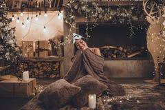 Den härliga asiatiska kvinnan bär sova den julträdet och spisen för maskering och för pyjamas det hemmastadda near i hemtrevlig i fotografering för bildbyråer