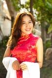 Den härliga asiatiska kvinnan i traditionell klänning, i att le, vänder mot. Arkivfoto