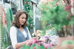 Den härliga asiatiska kvinnan köper blommor lyckligt från blomman royaltyfri bild