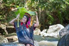 Den härliga asiatiska kvinnan med karen den traditionella klänningen undersöker på waen Arkivfoton