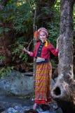 Den härliga asiatiska kvinnan med den thai traditionella klänningen undersöker på wat Arkivbilder