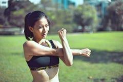Den härliga asiatiska kvinnan som sträcker henne muskler för henne, kör Royaltyfri Fotografi