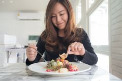 Den härliga asiatiska kvinnan tycker om att äta fruktsallad på tabellen i restaurang royaltyfri foto