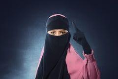 Den härliga asiatiska muslimkvinnan skyler in att peka med upprivna ögon Arkivfoton