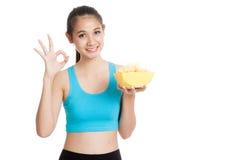 Den härliga asiatiska sunda flickan äter tecknet för showen för potatischiper det reko Royaltyfri Foto