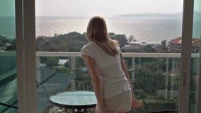 Den härliga attraktiva kvinnan öppnar glida-dörrar till balkongen Går utanför och sitter på koppla av för stol arkivfilmer