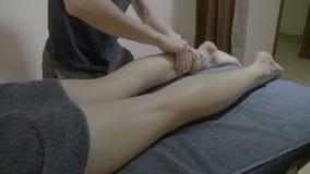 Den härliga attraktiva kvinnan på en brunnsortmitt som får henne ben, masserade anti-cellulite av en bra seende manlig terapeut - stock video