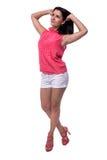 Den härliga attraktiva unga kvinnan i blus och korta kortslutningar ler sött och att lyfta hans handhår, den fulla längden Royaltyfri Fotografi