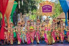 Den härliga Balinesefolkgruppen i färgrika sarongs ståtar på Arkivbild