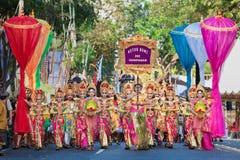 Den härliga Balinesefolkgruppen i färgrika sarongs ståtar på Royaltyfria Bilder