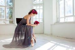 Den härliga ballerina som sirtting i långa grå färger Royaltyfri Bild