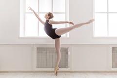 Den härliga ballerinen står i arabesquebalettposition arkivbilder