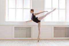 Den härliga ballerinen står i arabesquebalettposition arkivbild
