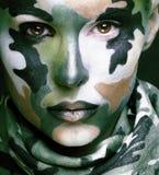 Den härliga barnmodekvinnan med militära stilkläder och framsidan målar sminket, kaki- färger, halloween beröm royaltyfri foto