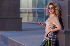 Den härliga barnmodekvinnan med shoppingpåsar nära shoppar fönstret som kallar den smarta telefonen som tonas Arkivfoto