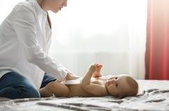 Den härliga barnmodern i den vita skjortan och jeans som sätter blöjan på gulligt nyfött, behandla som ett barn att förbereda sig Arkivbilder