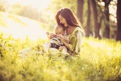 Den härliga barnmodern med henne behandla som ett barn sonen på naturen Stående royaltyfri bild
