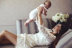 Den härliga barnmodern med långt mörkt hår som poserar med hennes lilla förtjusande, behandla som ett barn Royaltyfri Bild