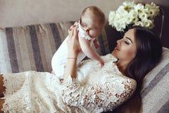 Den härliga barnmodern med långt mörkt hår som poserar med hennes lilla förtjusande, behandla som ett barn Royaltyfri Fotografi